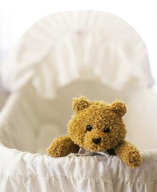 empty crib with teddy bear due to secondary and primary infertility